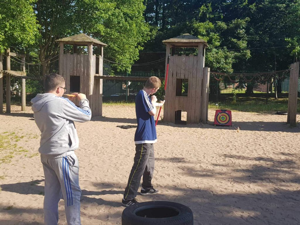 2 young people from behind. One of them is firing a bow and arrow at a target