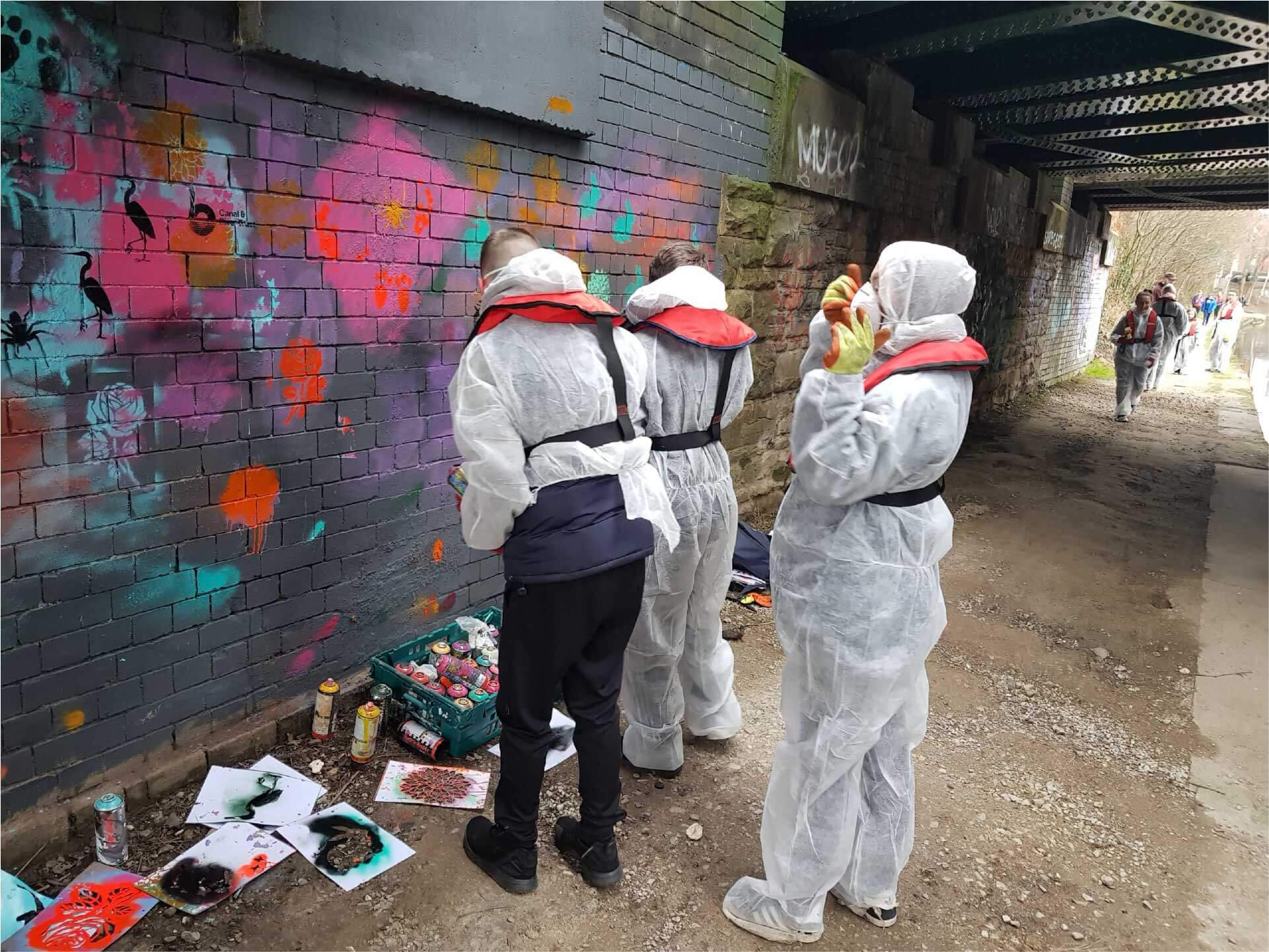 3 young people in protective clothing using spray-paint to paint a mural on a wall