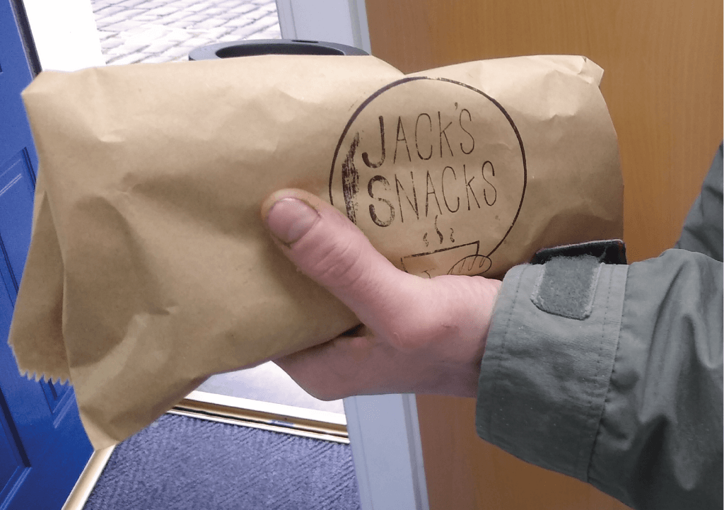 A close up photo of someone holding a sandwich in a Jack's Snacks bag