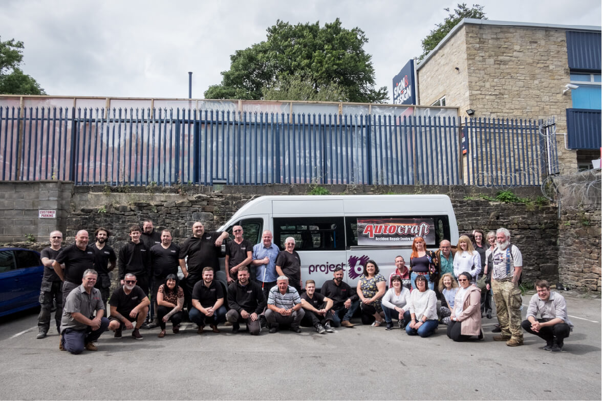 People from Project 6 and staff from Autocraft posing in front of a minibus